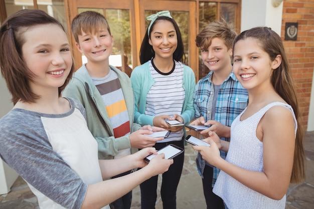 サークルに立って携帯電話を使用して笑顔の学校の学生の肖像画