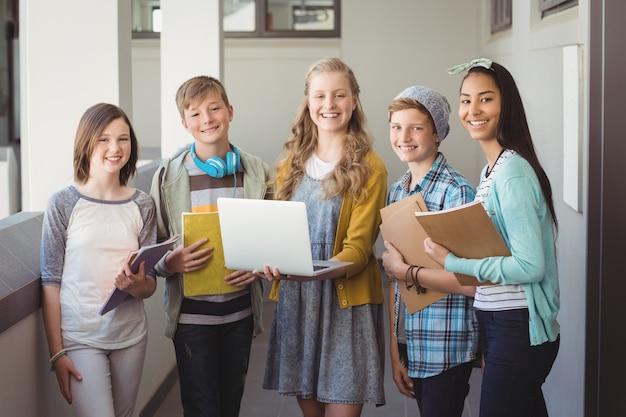 Портрет улыбающихся школьников, использующих ноутбук в коридоре