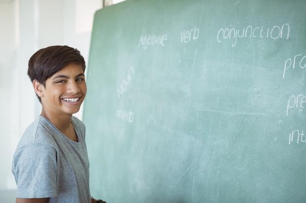 Портрет улыбающегося школьника, стоящего возле доски в классе
