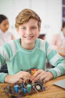電子プロジェクトに取り組んでいる少年の笑顔のポートレート