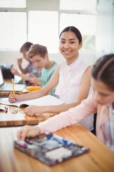 Портрет улыбающейся школьницы, делающей домашнее задание в классе