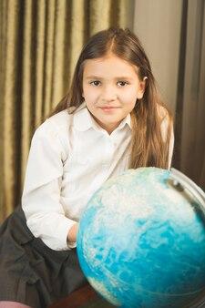キャビネットで地球儀とポーズをとって笑顔の女子高生の肖像画