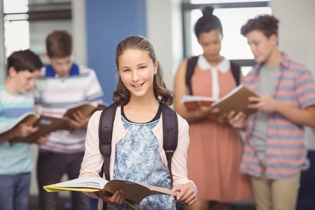 Портрет улыбающейся школьницы, стоящей с книгой в классе