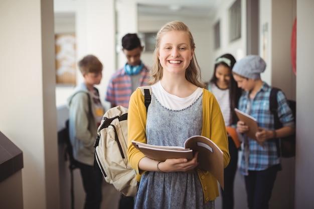 Портрет улыбающейся школьницы, стоящей с ноутбуком в коридоре