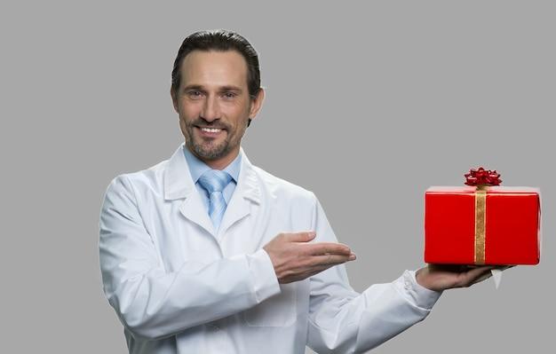 Портрет улыбающегося ученого, показывающего подарочную коробку. веселый человек в белом халате, предлагающий красную праздничную подарочную коробку на сером фоне.