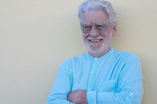 Портрет улыбающегося старшего бородатого мужчины на четком желтом фоне