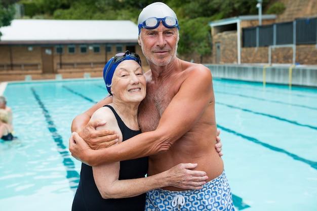 Портрет улыбающейся старшей пары, обнимающей друг друга у бассейна