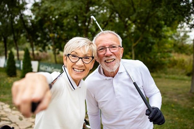 골프장에서 웃고 있는 노부부의 초상화는 게임 토너먼트를 관람하는 것을 즐긴다