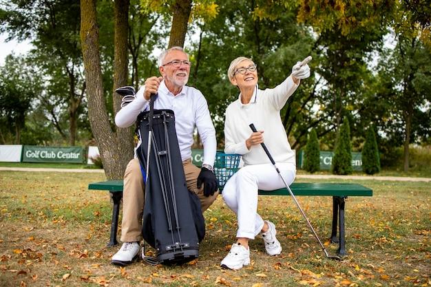 Портрет улыбающейся старшей пары на поле для гольфа наслаждается просмотром игрового турнира