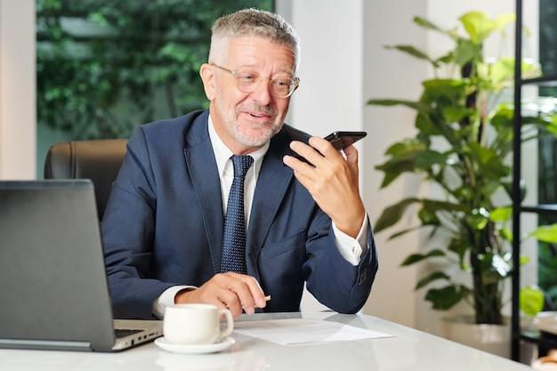 그의 동료를 위해 음성 메시지를 녹음하는 웃는 수석 기업가의 초상화