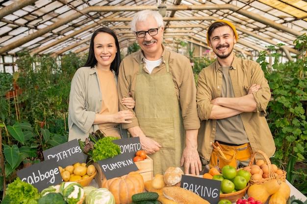 農家の市場で熟した野菜とテーブルに立っている笑顔のシニア庭師と彼の若い多民族アシスタントの肖像画