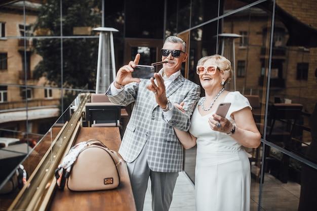 Портрет улыбающегося старшего мужчины и женщины, сидящих в объятиях снаружи