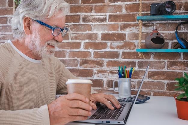 Портрет улыбающегося старшего человека, использующего портативный компьютер у себя дома. кирпичная стена на фоне