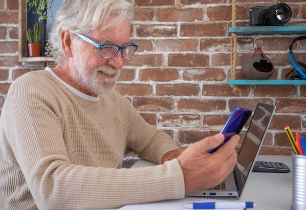 Портрет улыбающегося старшего мужчины с помощью мобильного телефона и портативного компьютера дома фоне кирпичной стены