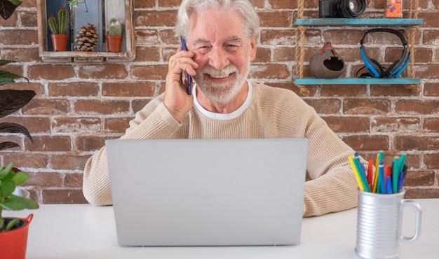 Портрет улыбающегося старшего мужчины с помощью мобильного телефона и портативного компьютера дома кирпичная стена o