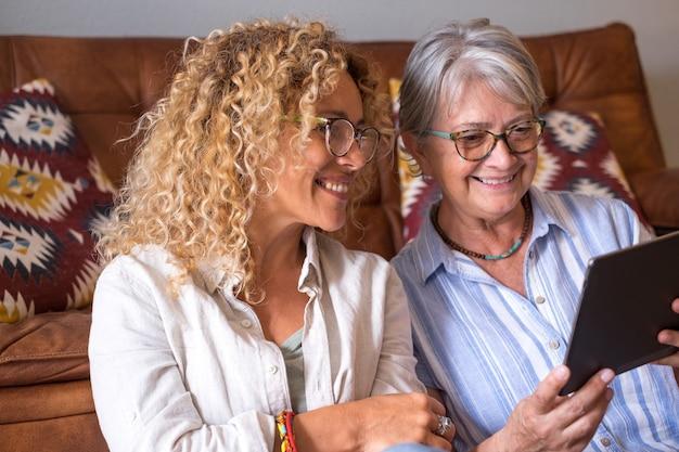 디지털 태블릿을 사용하여 집에 앉아 웃고 있는 노모와 성숙한 금발 딸의 초상화