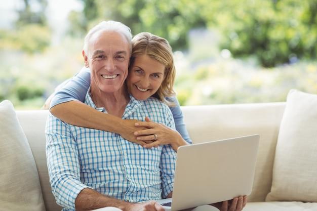 Портрет улыбающейся старшей женщины, обнимающей мужчину в гостиной во время использования ноутбука