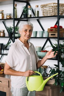 Portrait of smiling senior woman holding watering can touching plant at home