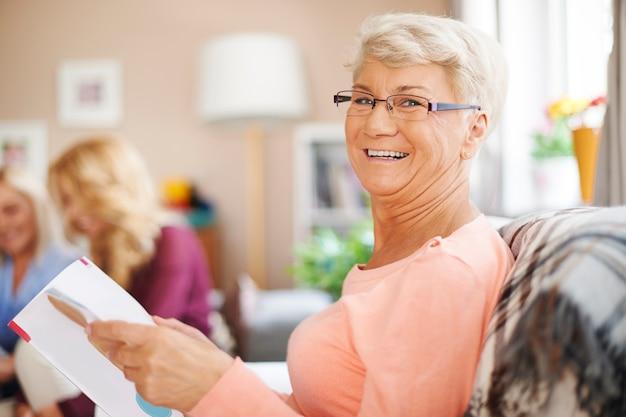 Портрет улыбающейся старшей женщины, читающей газету