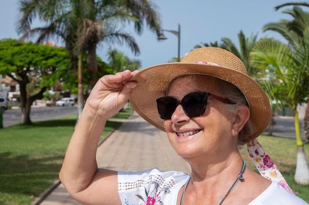식물과 야자수가 있는 쾌적한 공원에서 밀짚모자를 쓴 웃고 있는 노년 여성의 초상화 - 여름 방학 동안 활동적인 노인의 개념