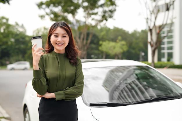 外の車の近くに立ちながら、マグカップの飲み物を飲む笑顔のセクシーな女性のポートレート