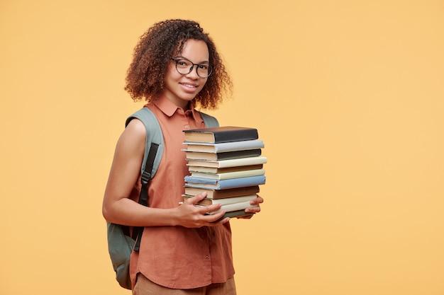 黄色の背景に本のスタックを運ぶバックにランドセルを持つスマートなアフリカ系アメリカ人の学生の女の子の笑顔の肖像画