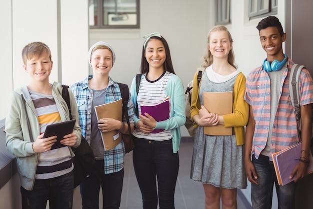 廊下にノートとランドセルを持って立っている笑顔の学生の肖像画