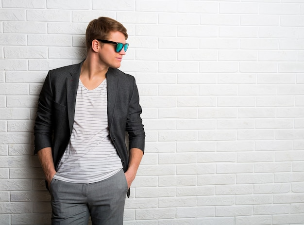 現代のオフィスのレンガの壁に立っているサングラスで笑顔のスタイリッシュな男の肖像画。