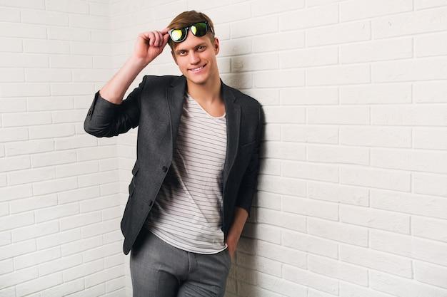 Портрет улыбающегося стильного человека, стоящего у кирпичной стены в современном офисе