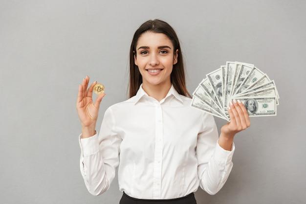 Портрет улыбающейся успешной женщины в белой рубашке и черной юбке, держащей биткойн и много долларовых купюр, изолированные на серой стене