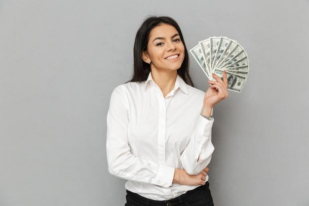 Портрет улыбающейся успешной женщины с длинными каштановыми волосами в офисной одежде, улыбающейся и держащей долларовые банкноты, изолированные на сером фоне