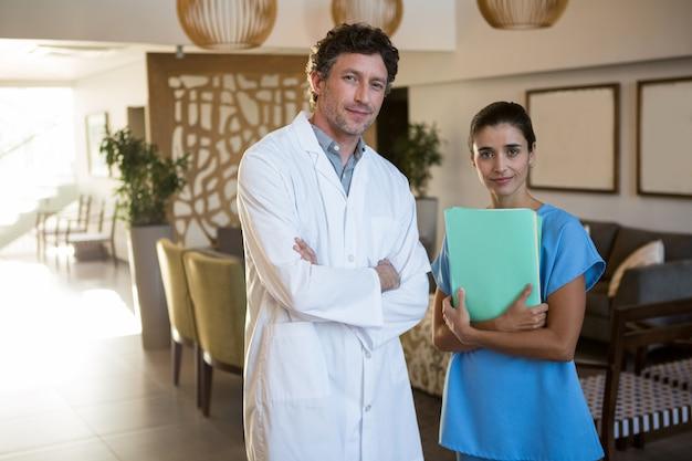笑顔の外科医と腕を組んで立っている医者の肖像画