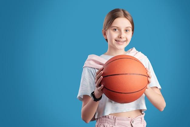 Портрет улыбающейся девочки-подростка, держащей баскетбол