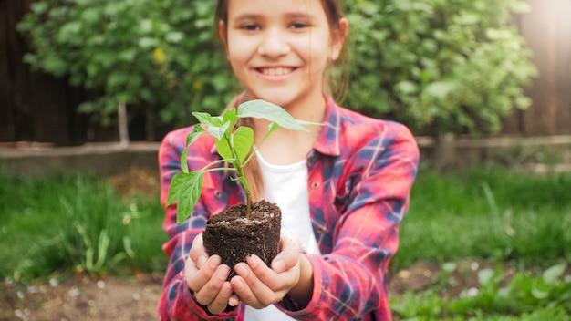 Портрет улыбающейся девочки-подростка, держащей в руках саженец цветка или дерева.