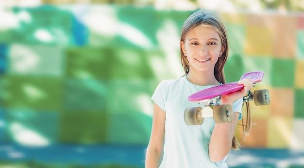 공원에서 분홍색 스케이트보드를 들고 웃고 있는 10대 소녀의 초상화