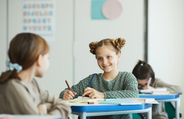 学校の教室、コピースペースで友人と話している笑顔の10代の少女の肖像画