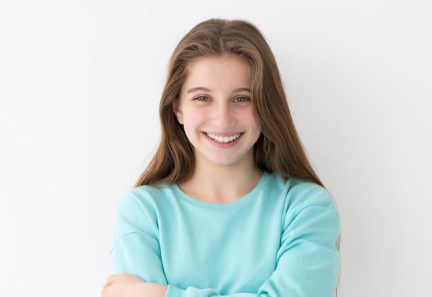 白い壁に長いゆるい髪を持つ笑顔の 10 代の少女の肖像画