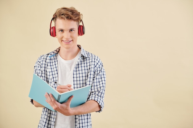 Портрет улыбающегося студента-подростка в наушниках, слушающего учителя английского языка и делающего заметки в тетради
