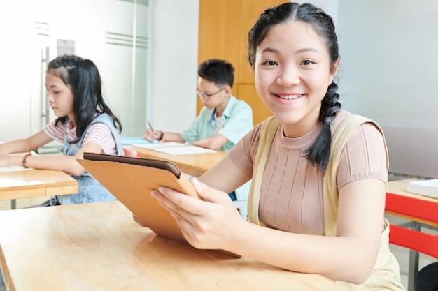 Портрет улыбающейся вьетнамской девочки-подростка с помощью цифрового планшета в классе