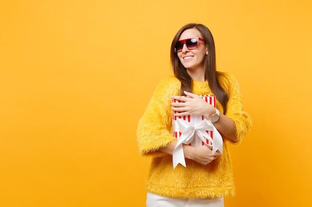 明るい黄色の背景で隔離のプレゼント、ギフトと赤い箱を抱き締める赤い眼鏡で笑顔の優しい若い女性の肖像画。人々の誠実な感情、ライフスタイルのコンセプト。広告エリア。