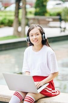 噴水のそばに座って、音楽を聴き、ラップトップで作業している笑顔のベトナムの10代の少女の肖像画