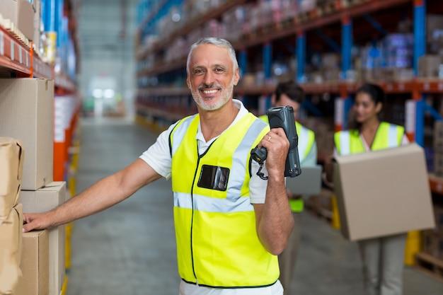 Портрет улыбающегося склада работника сканирования коробки