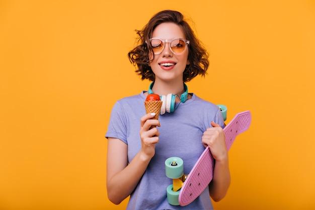 Longboard를 들고와 디저트를 먹고 웃는 백인 여자의 초상화. 스케이트 보드와 아이스크림 갈색 머리 매력적인 여자.