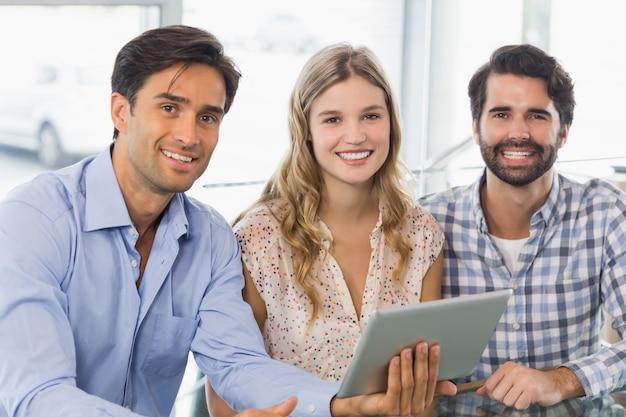 デジタルタブレットを使用して笑顔の女性と2人の男性の肖像画