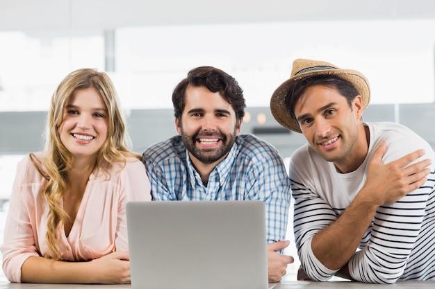 ラップトップを使用して笑顔の女性と2人の男性の肖像画