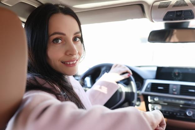 자동차 살롱에서 웃는 여자 드라이버의 초상화