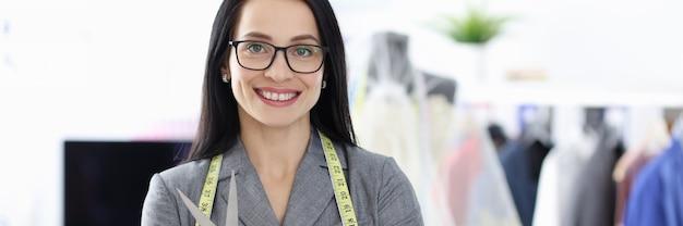 彼女の手にはさみを持って笑顔の女性のファッションデザイナーの肖像画は、サービスの概念を調整します