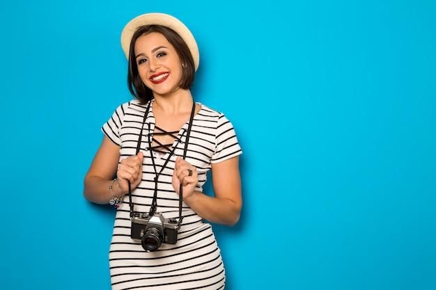 Портрет улыбающейся женщины моды со старой камерой на