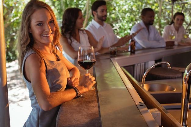 カウンターで赤ワインのグラスを持つ笑顔の女性の肖像画