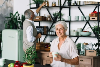 Portrait of smiling woman holding coffee cup sitting in front of man taking bottle from shelf